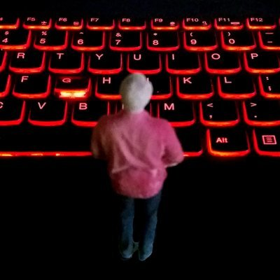 A tiny man stands before an enormous glowing keyboard.