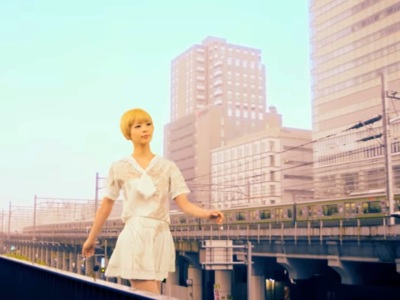 A gigantic Japanese woman strides carelessly through Tokyo beside a monorail.