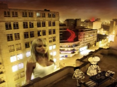 A gigantic woman stands between buildings, peering onto the roof of one.