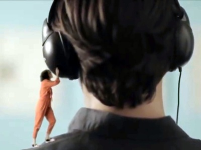 A tiny woman stands on a man's shoulder, trying to listen to his headphones.