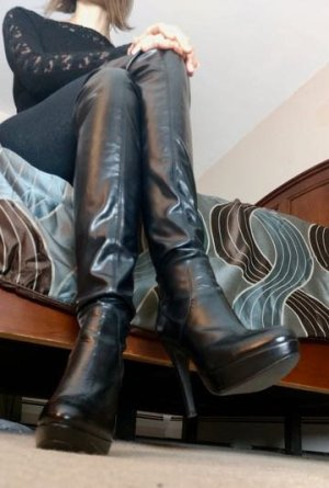 Giantess Nyx features some knee-high, high-heeled leather boots.