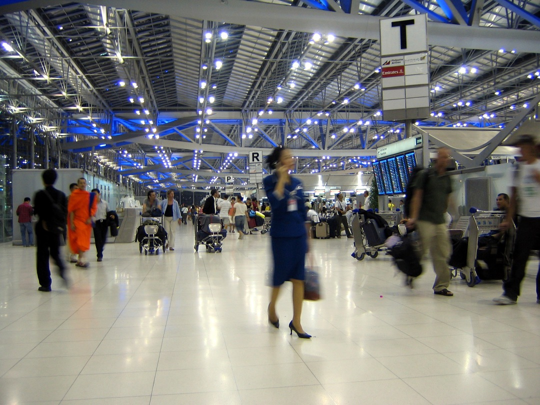 Travelers wander through a futuristic-looking Bangkok airport.