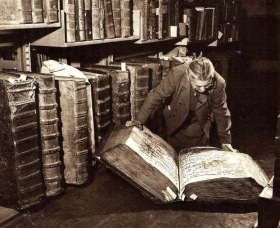 An old woman in a suit reads from an enormous book nearly as big as she is, in a 1940 photo.