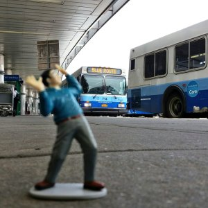 A tiny man is terrified by tremendous mass transit buses.
