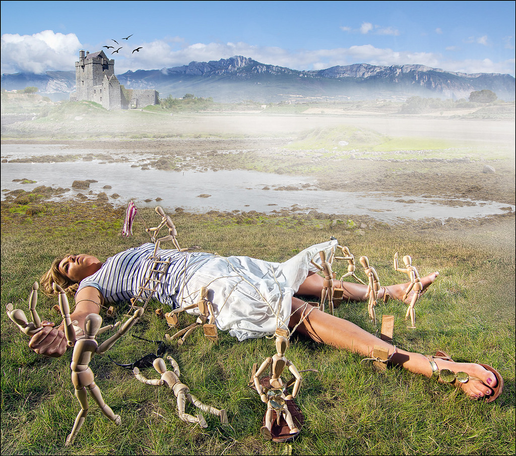 A giantess reclines on a grassy field, while wooden dolls crawl all over her.