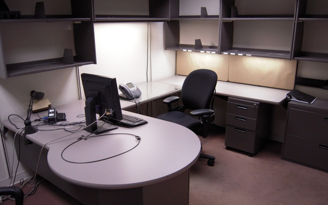 Empty corporate office, nothing on the shelves, monitor and keyboard sitting on bare desk.