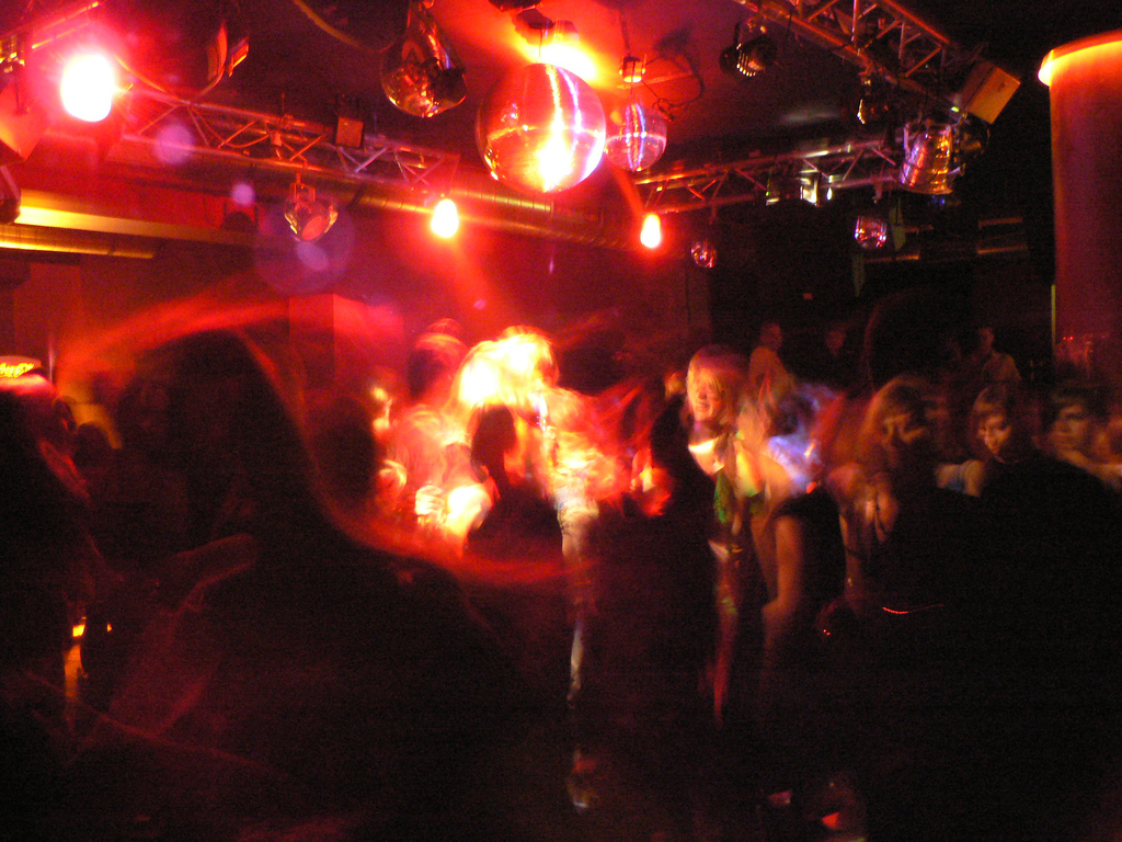 Yellow, orange, red streaks of light in a darkened dance club, blurry images of people dancing. A dance club in Stuttgart, photo by Curran Heller.