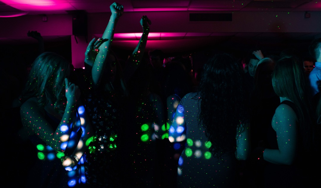 Young women dancing in a darkened club, with speckled laser lights running over them.