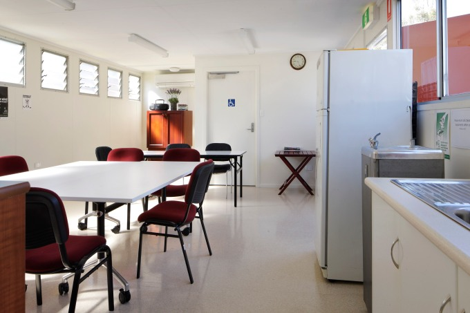 A spacious, clean, white kitchenette and dining area for a corporate office.