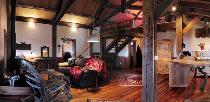 Messy, decorative artist's loft with hardwood floors, a carved armoire, blankets thrown over a plush couch, and dark wood support beams against white brick walls.