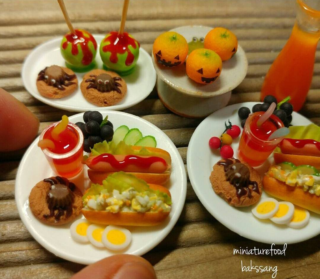 Polymer clay miniatures of hot dogs, cookies, caramel apples, eggs, and other picnic-style foods.