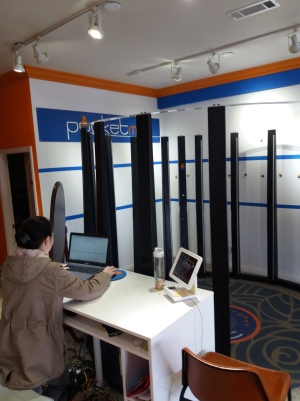 A woman prepares the computer program that will coordinate a ring of 90 cameras, mounted on tall poles, to take a 3D portrait.