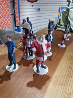 A plain wooden shelf features a selection of a dozen figurines, including children, families in matching outfits, and Santa Claus.