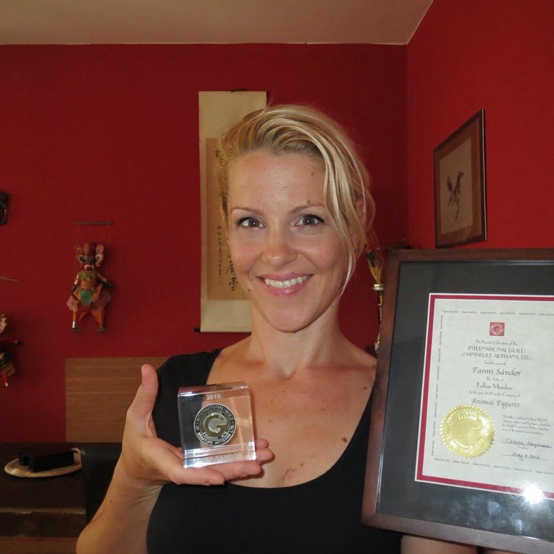 Fanni Sandor holds her Fellow award, standing in her studio.