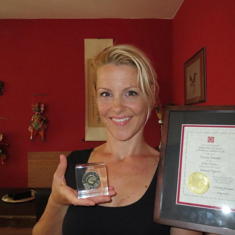 Fanni Sandor holds her Fellow award, standing in her studio.