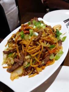 A big, overloaded plate of thick noodles and sliced, sauteed beef with vegetables.