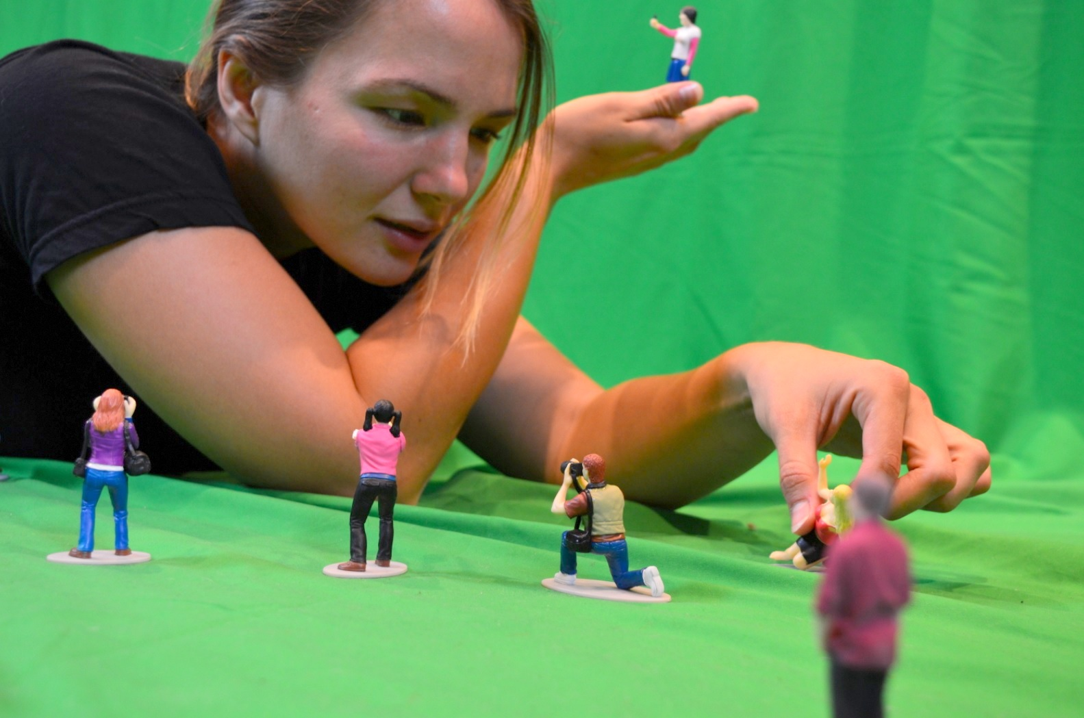 The model Koa leans over a selection of tiny people, interacting with their expressions.
