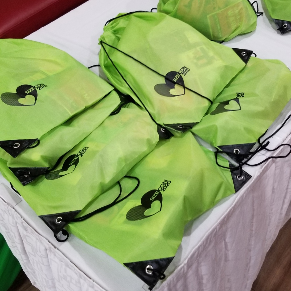 "Several green nylon string backpacks marked ""SizeCon"" rest on a white tablecloth."